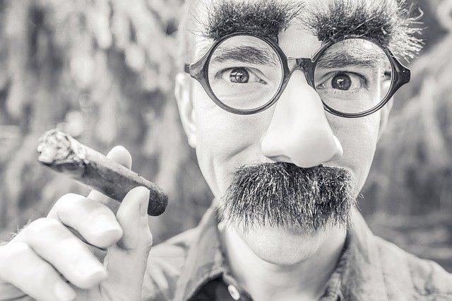 muž v masce kouřící doutník, černobílá fotografie.jpg